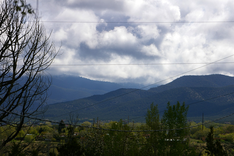 Utility lines slicing up the view of early morning clouds across the valley near Taos